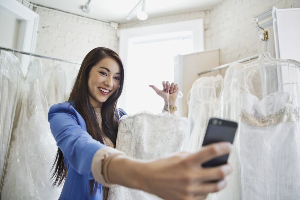 Young woman taking self portrait with wedding dress in bridal store