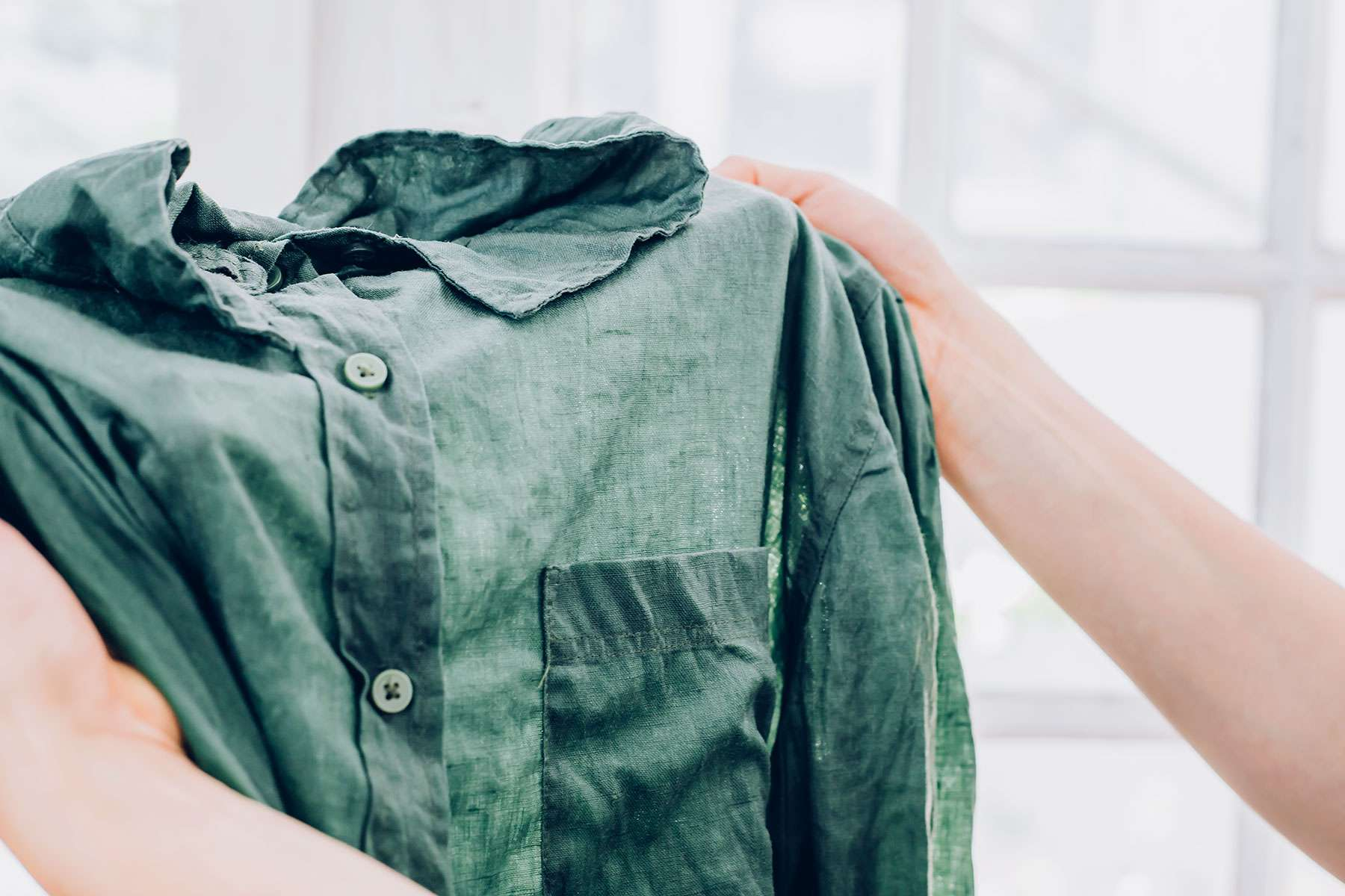Green collared shirt checked for stains after soaking