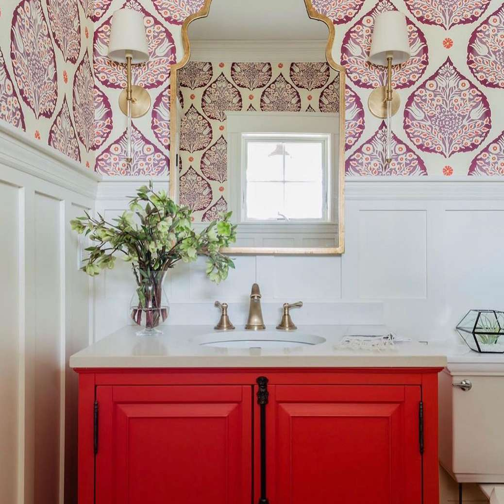 Bathroom with red vanity and pink wallpaper