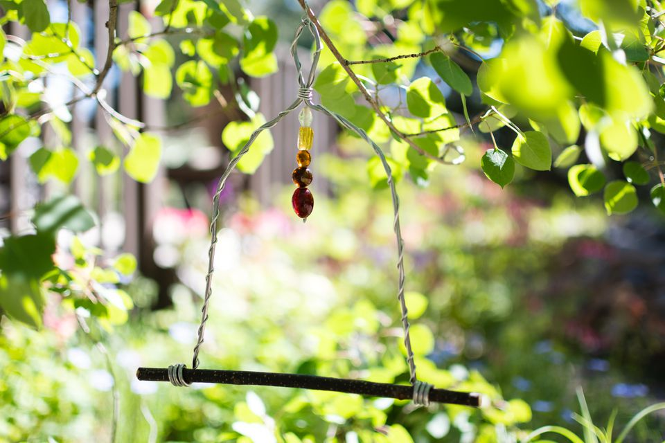 Hummingbird swing with beads hanging in the middle surrounded by tree branches