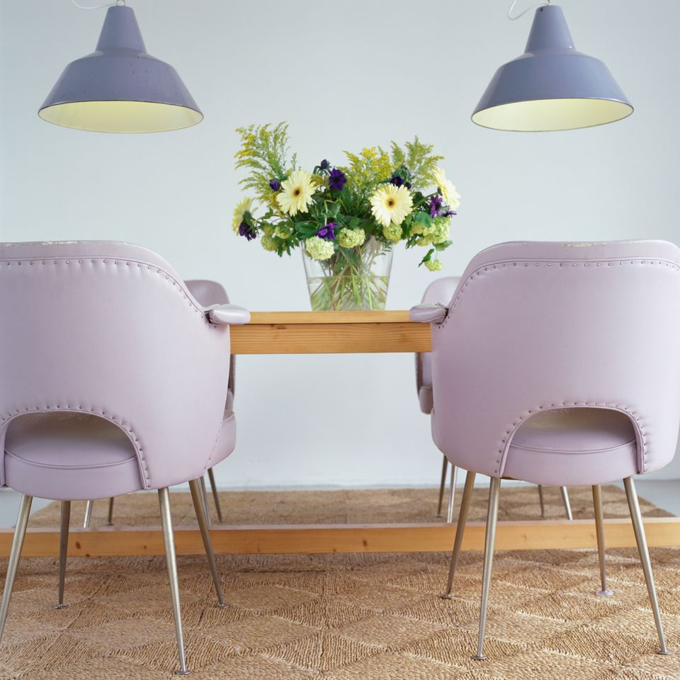 Upholstered orchid chairs with nailhead trim pop against this blond dining table.