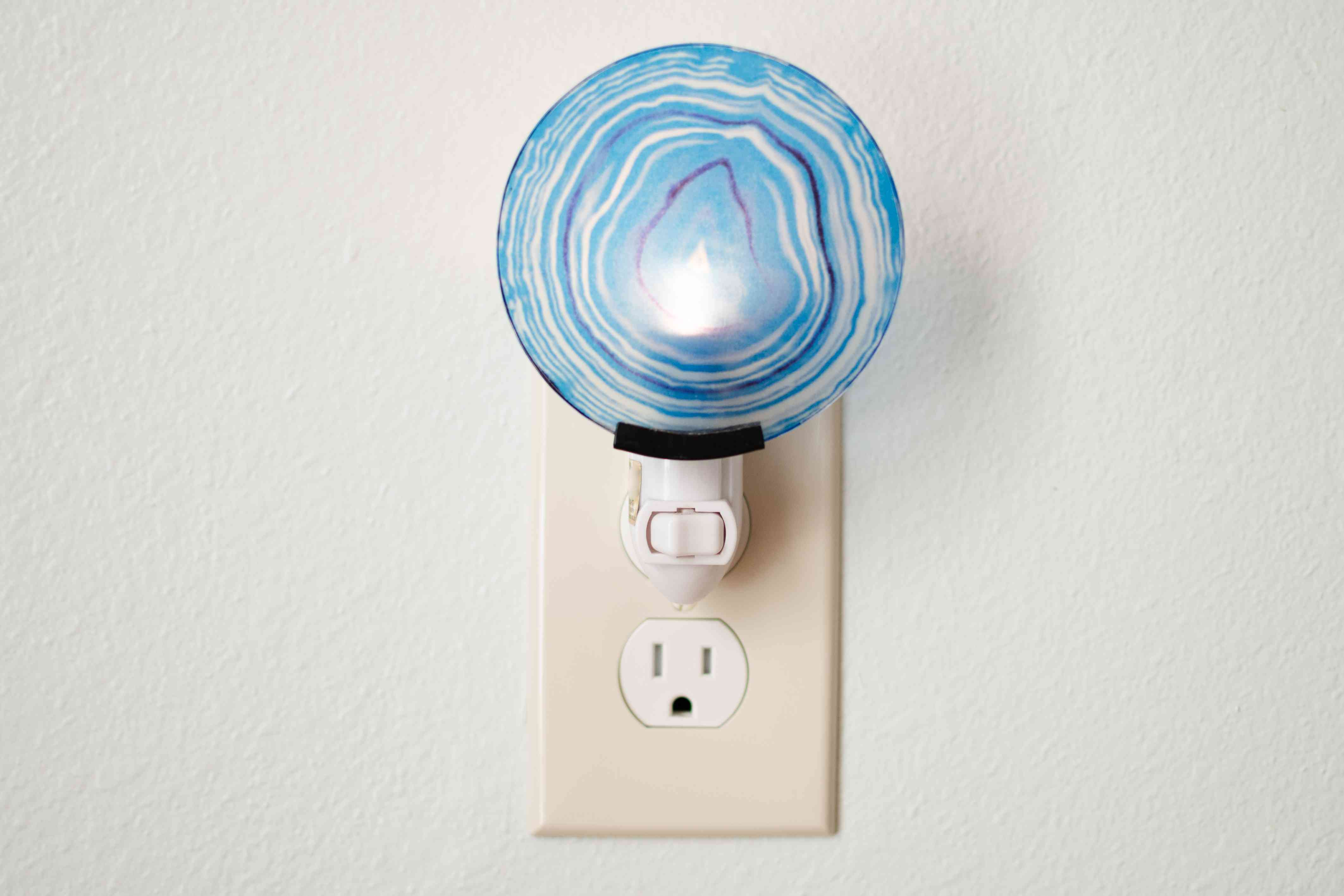 Blue circular plug-in light connected to electrical outlet