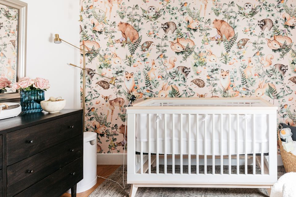 Nursery room with animal and foliage wallpaper next to white crib and dark brown dresser
