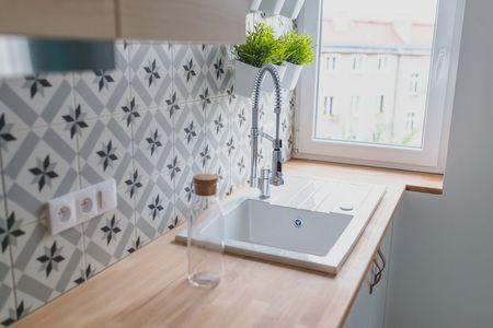 White Kitchen Sink With Decorative Backsplash Tiles