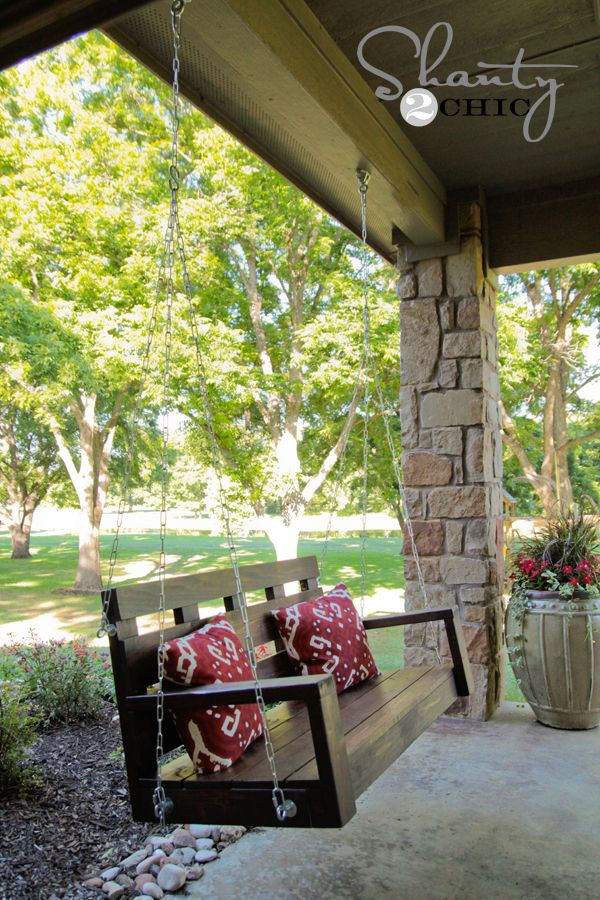 A wooden porch swing with red pillows