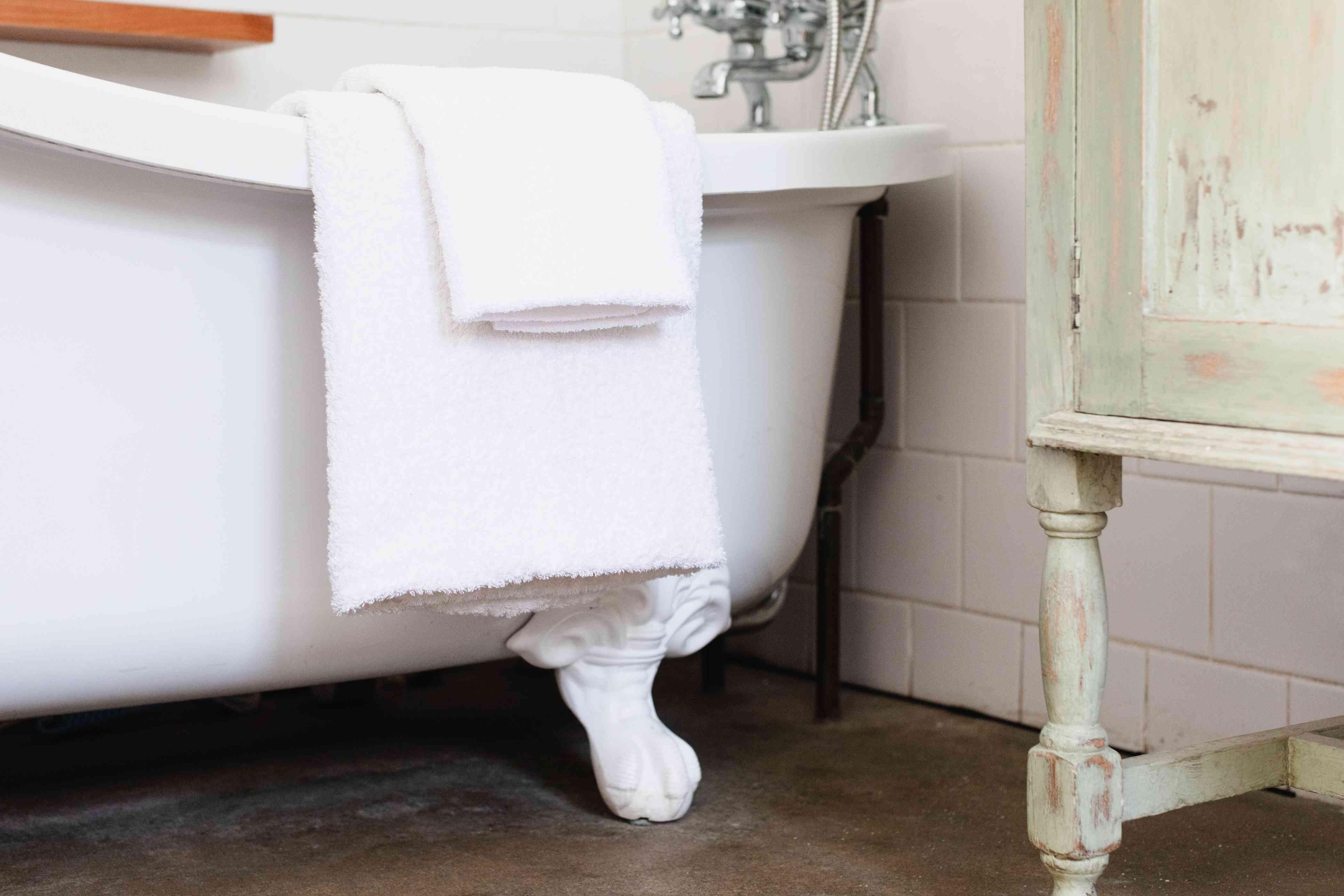 Folded fresh towels hanging over bath tub