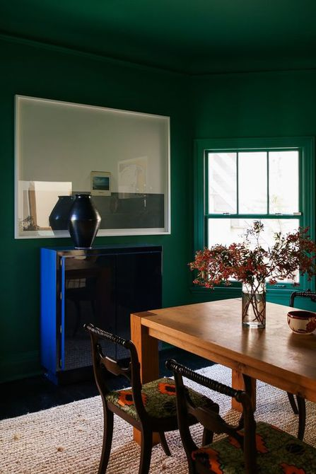 Comedor moderno con paredes verdes y techo