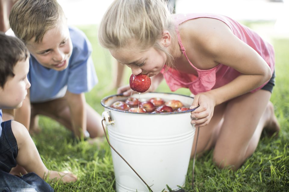 Girl trying to take apple out of bucket with water