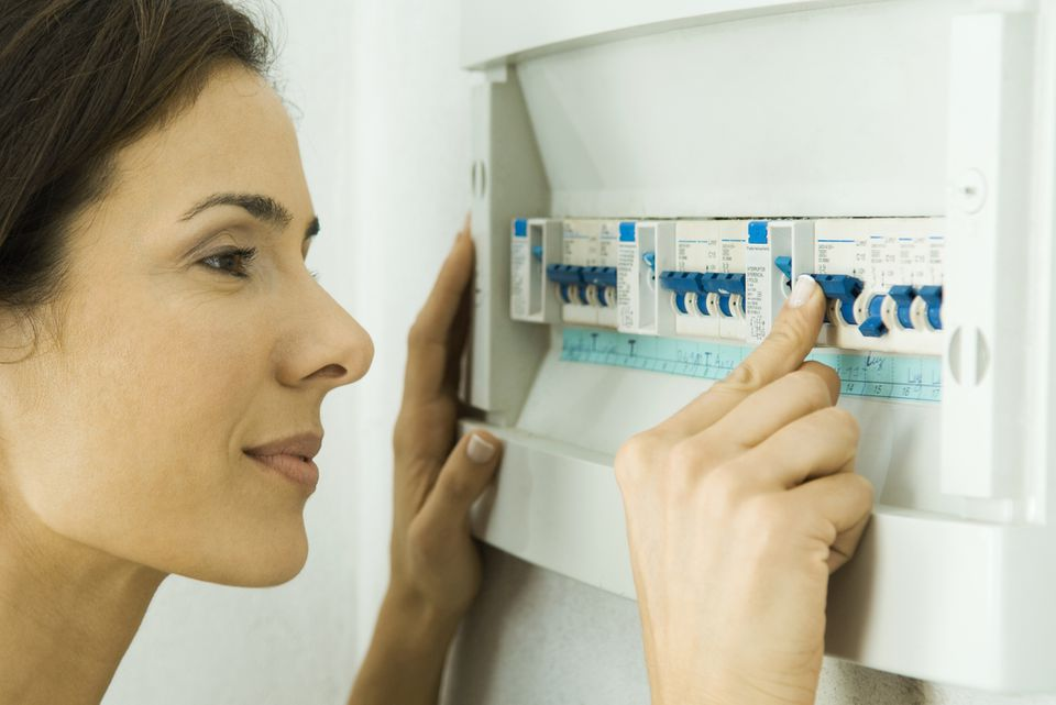 Woman looking at a fusebox