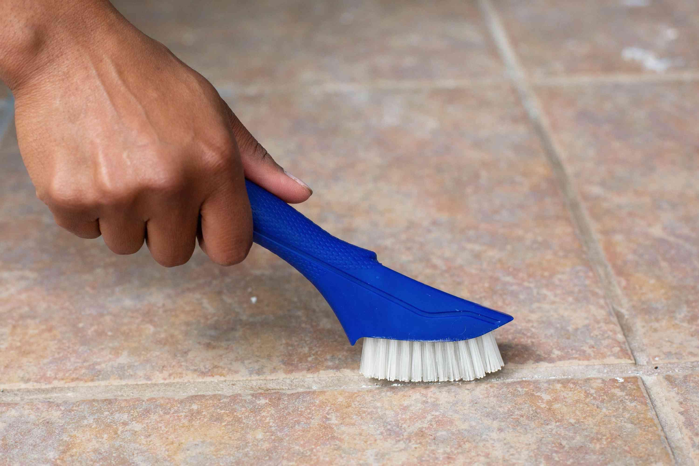 Blue hand-held brush cleaning grout between tile floor