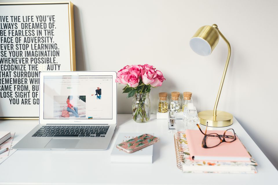 colorful workspace with rose, artwork, and laptop