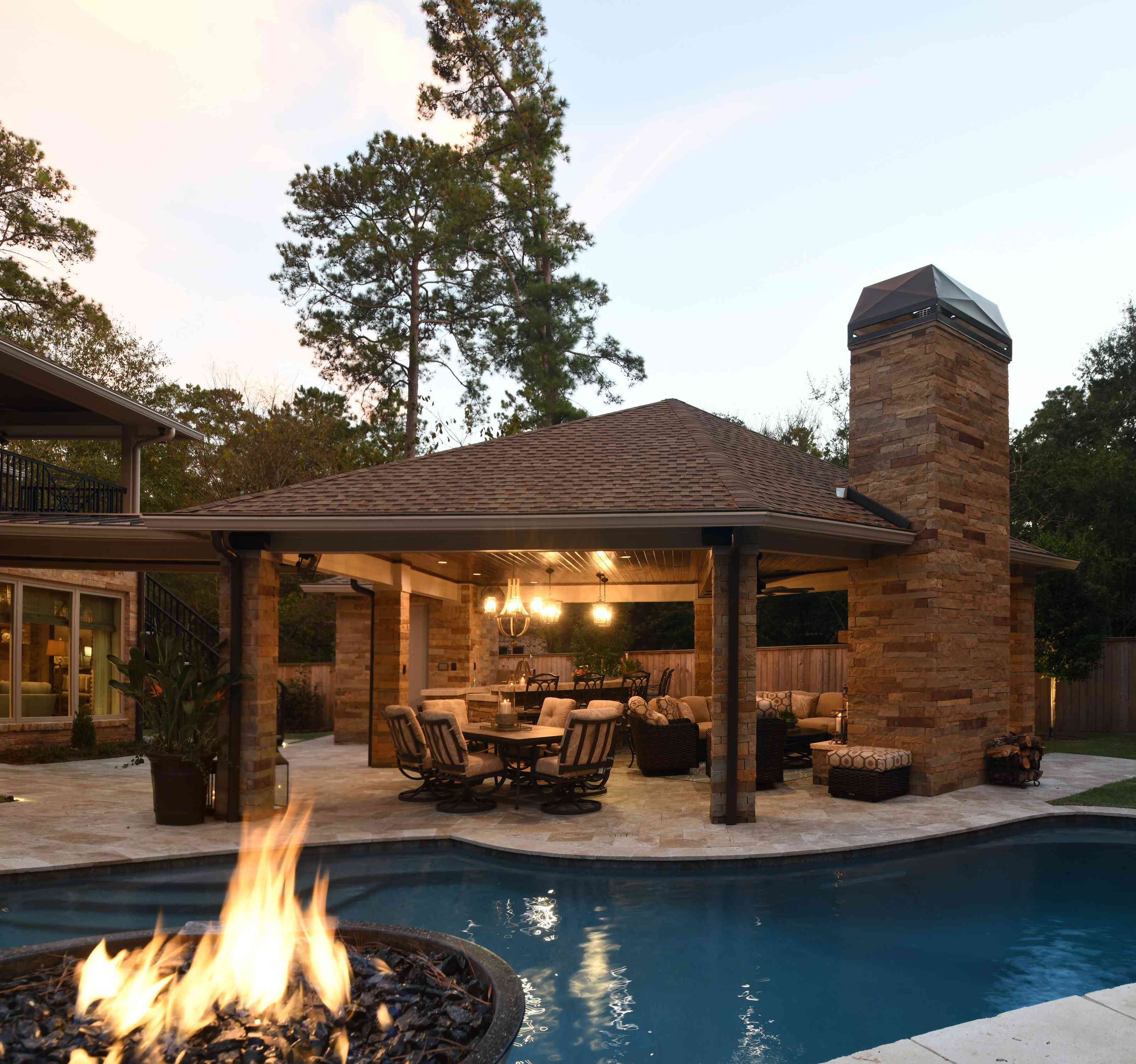 patio space features lighting, a fire pit, and a pool