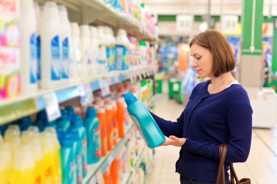 Woman reading ingredients on detergent