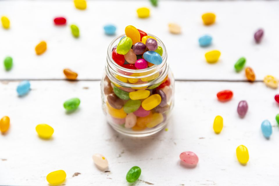 Glass of colourful sweet jellybeans on white wood