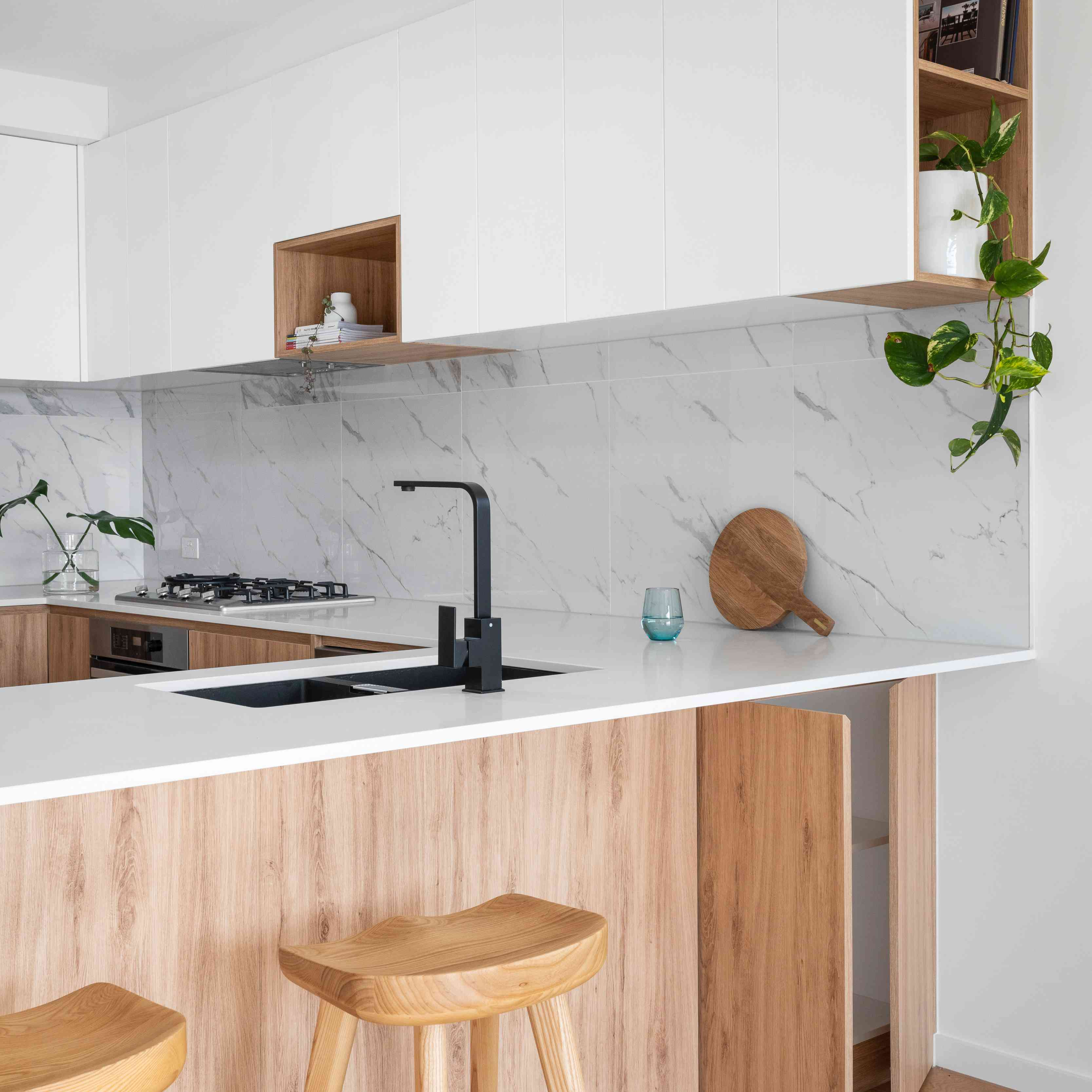 modern kitchen with marble, white and wood cabinets