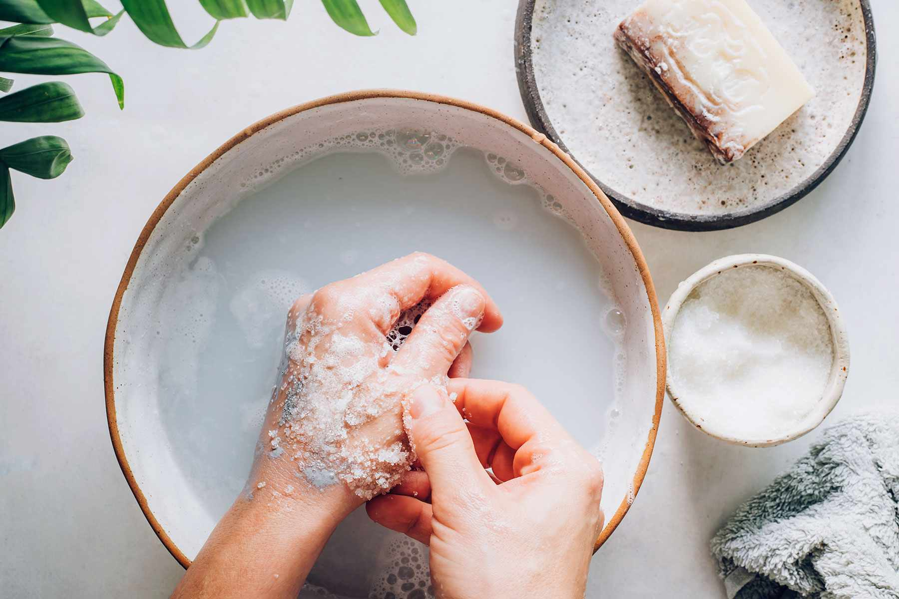 Table salt added to soap and water mixture in bowl to rub paint off hand