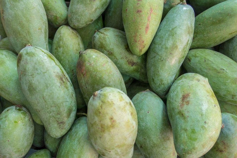 Fresh green unripe mangoes for sale in supermarket.