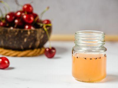 Fruit flies in a glass jar of vinegar in front of bowl of cherries