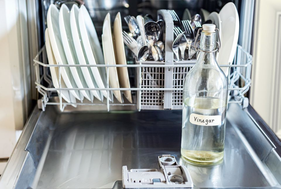 Glass bottle of vinegar sitting on opened dishwasher door with tray of dishes behind