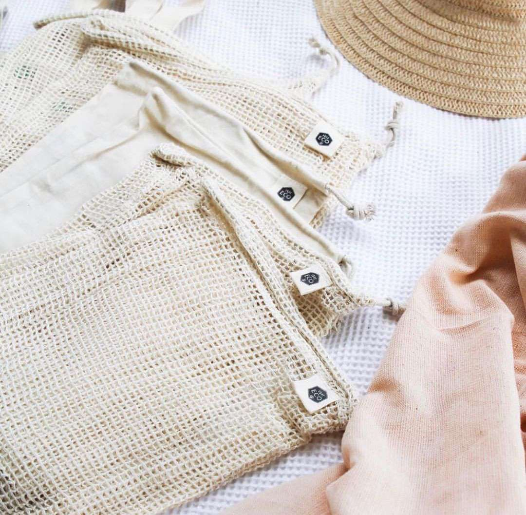 Eco-friendly bags next to a piece of fabric and a sun hat