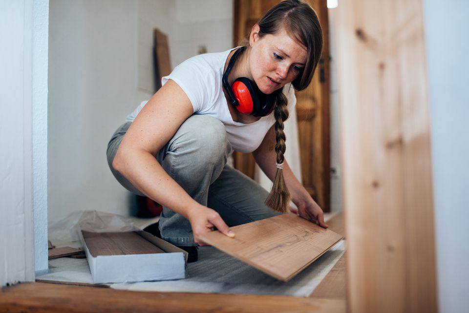 Woman installing laminate floor
