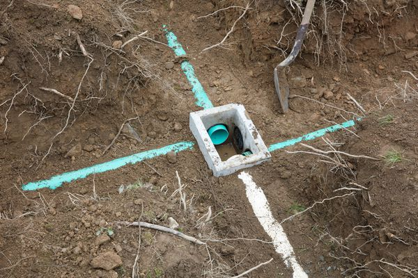 Leach line blue and white pipes centered with square cement holder in ground