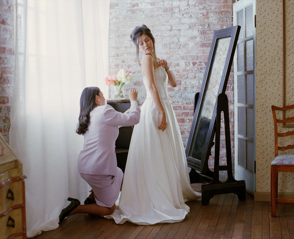 Woman adjusting bustle on bride