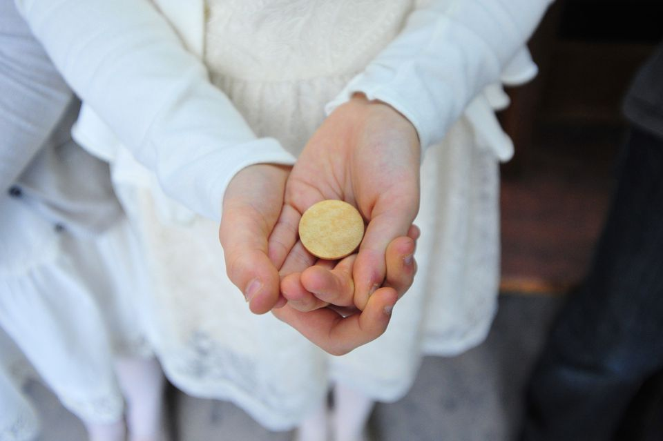 Someone in a long-sleeve white dress holding out hands holding a round communion cracker.