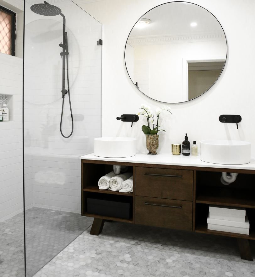 Updated bathroom with gray marble floor and large circle mirror above double vanity.
