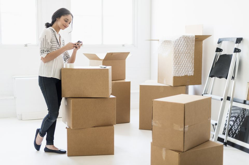 Young woman standing among boxes in new home and using mobile phone