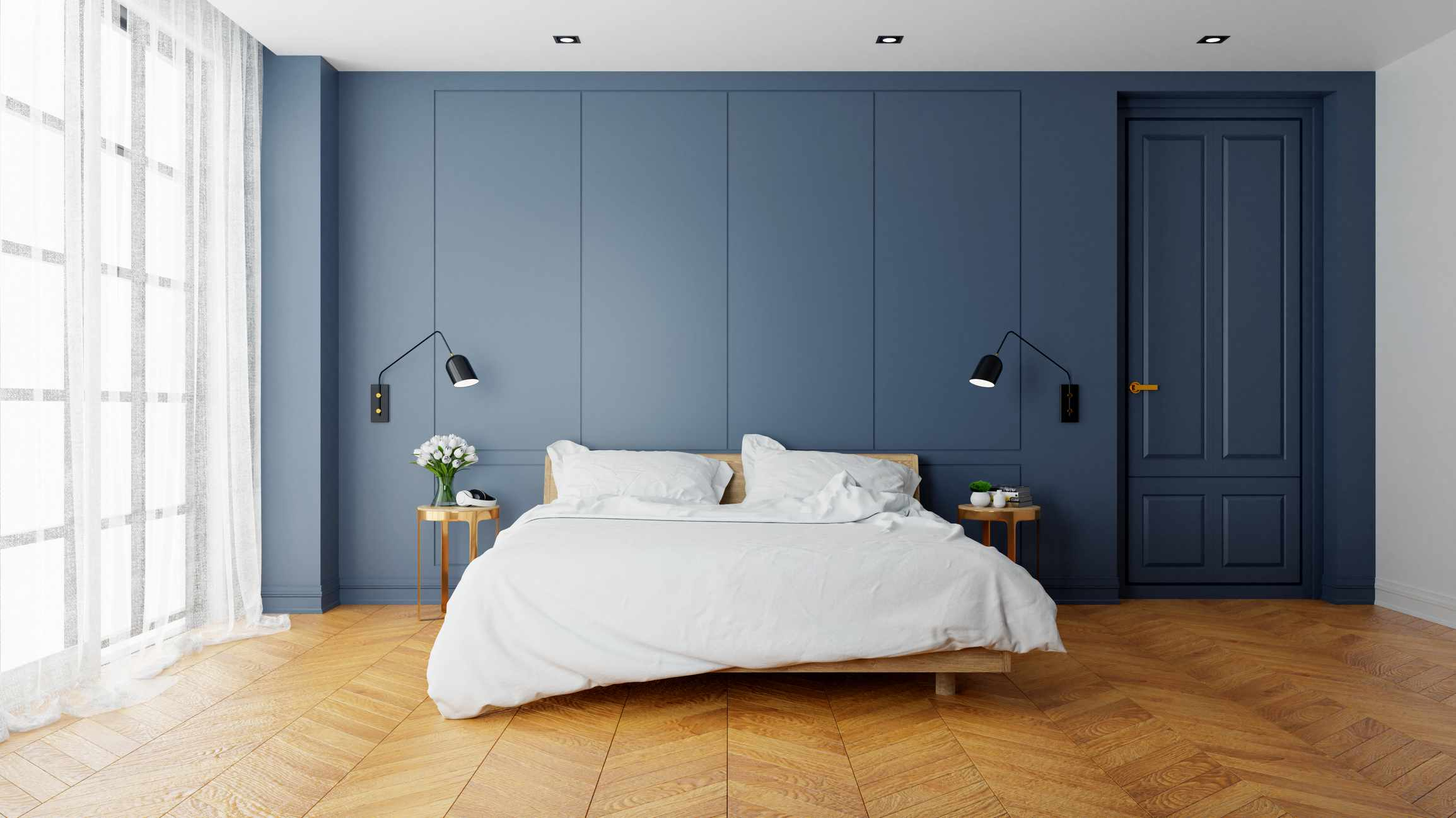 A soothing blue bedroom with a white bed.