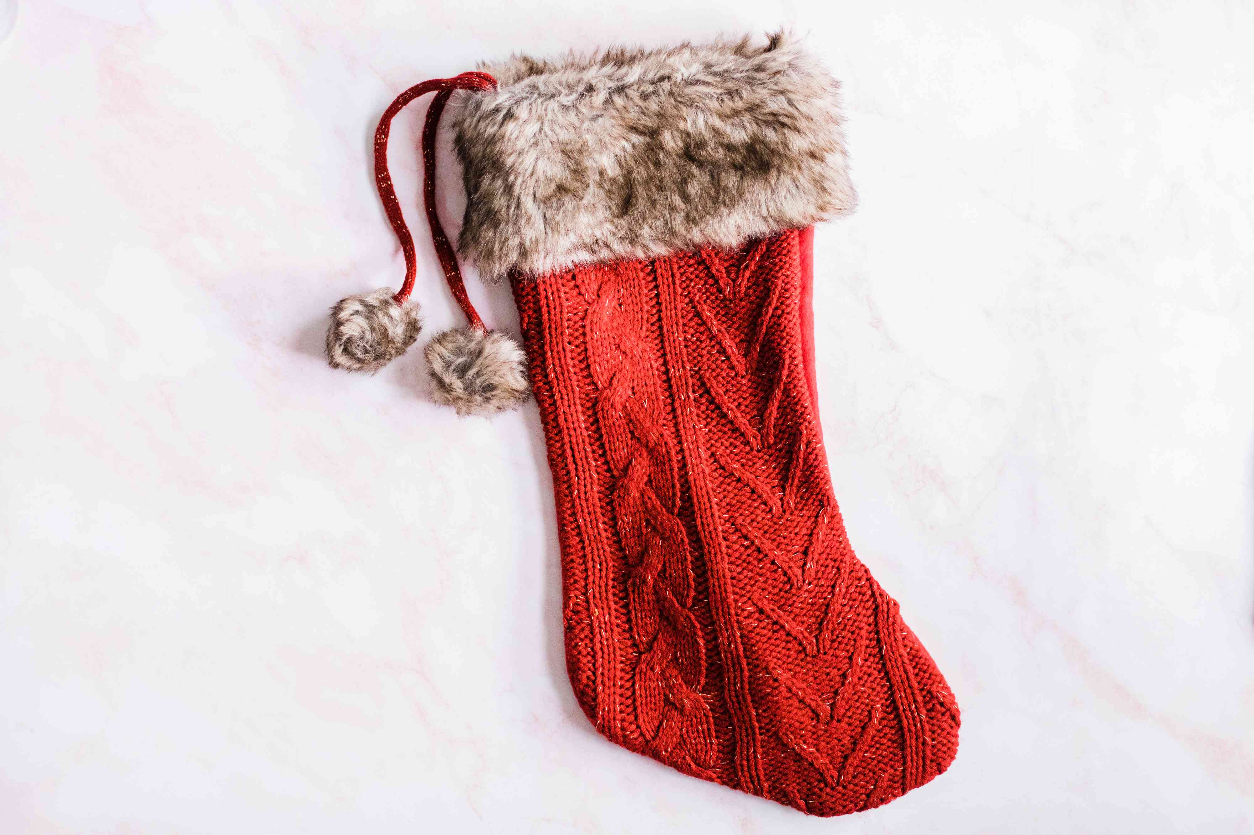 Red Christmas stocking on white surface