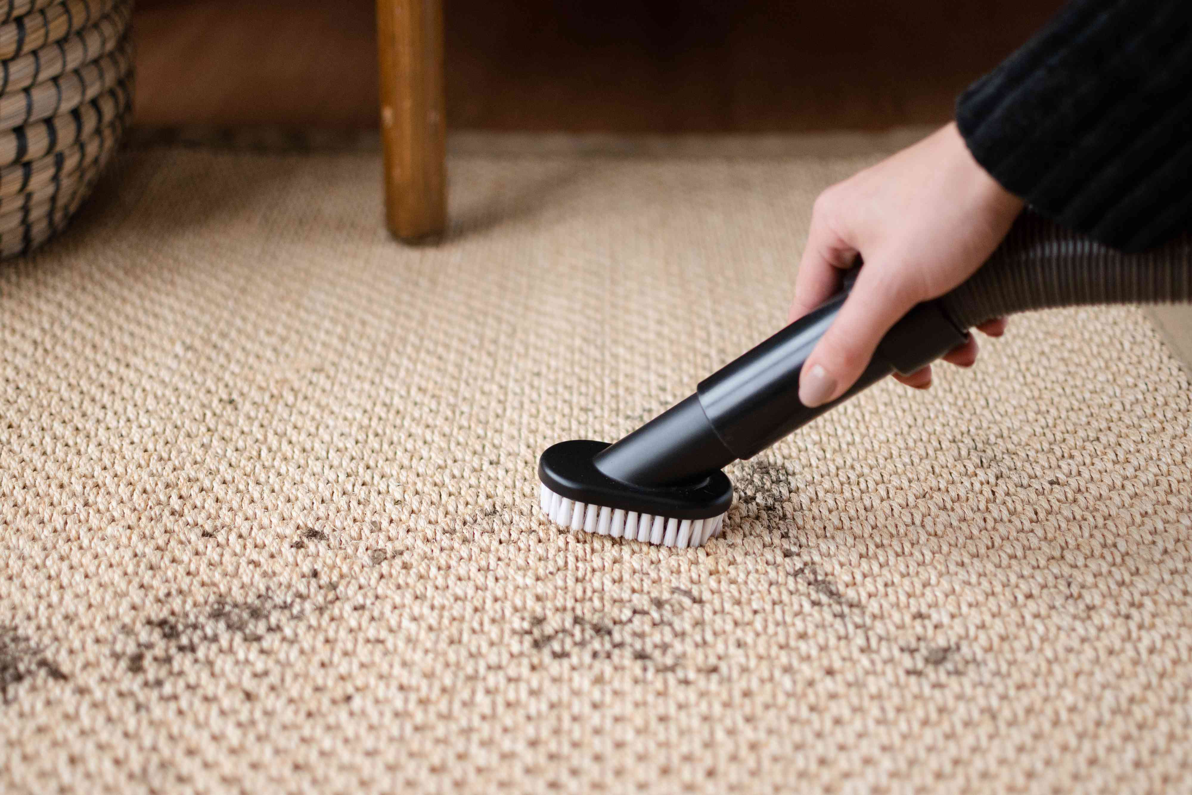 Tan sisal rug with loose dirt being vacuumed with hose attachment closeup
