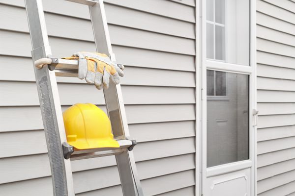 Ladder leaning against a house with a hard hat and gloves.