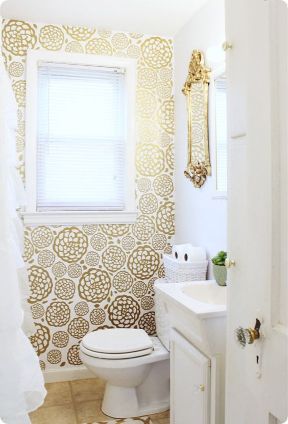 A bathroom with a wallpapered wall by the toilet
