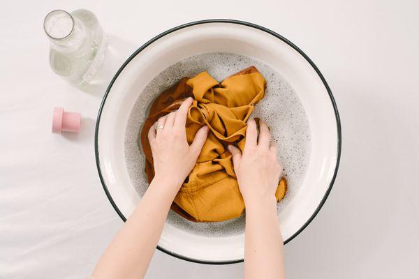 Someone soaking a garment in a basin