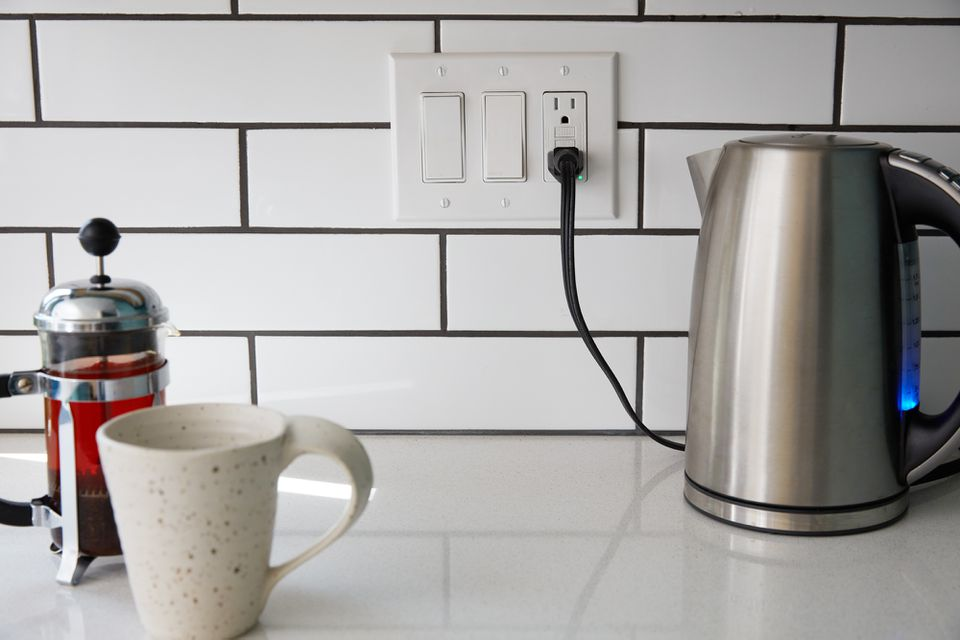 Kitchen outlet with electric kettle across from mug and french press coffee maker