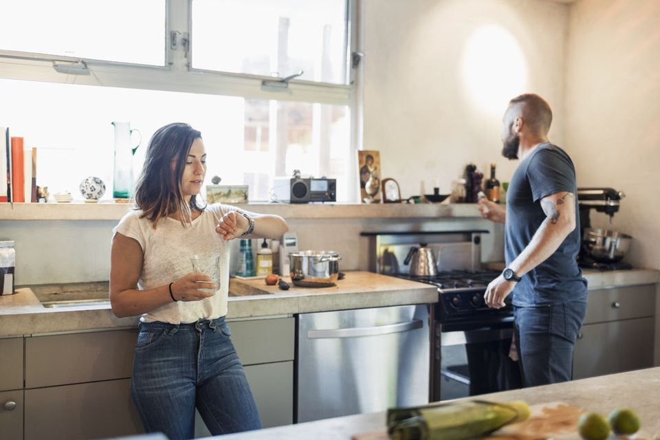 Woman checking time while man looking through window in kitchen