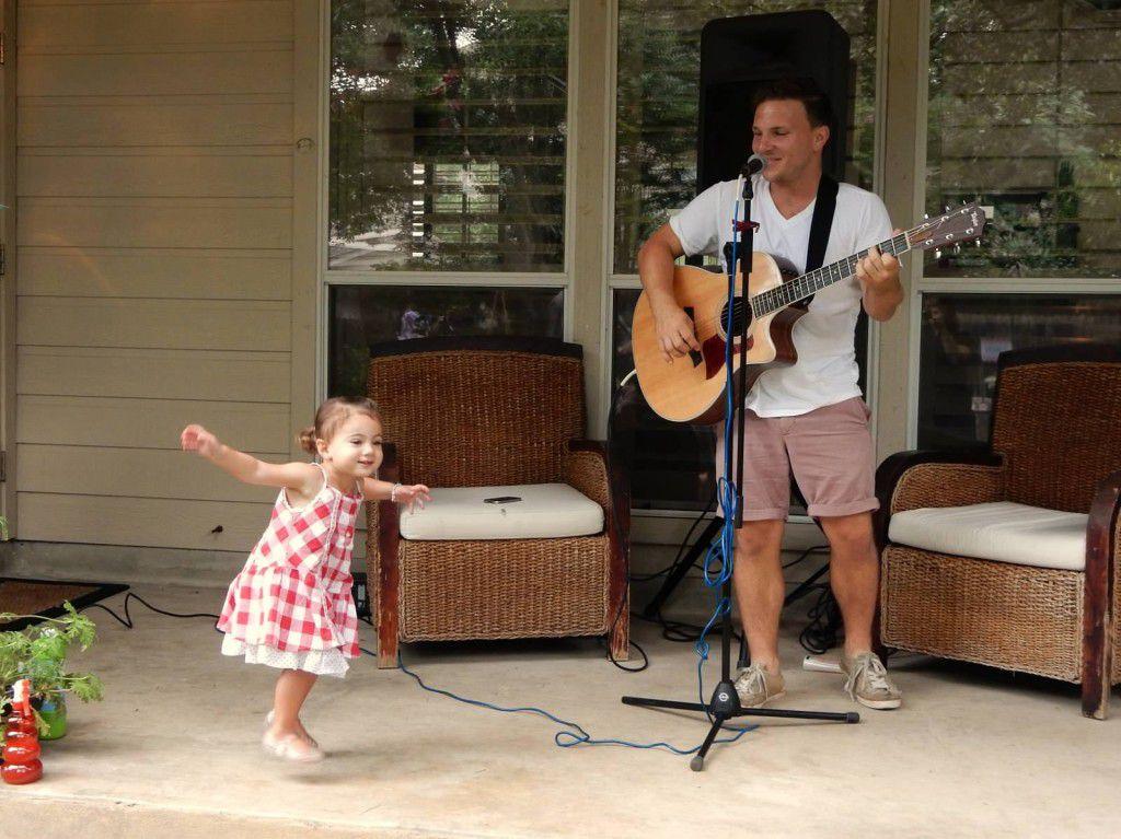 Un hombre tocando con una guitarra y una niña