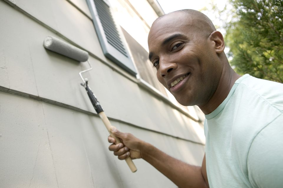 Man Painting House Exterior with Roller