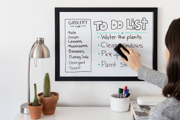 Small whiteboard above desk with grocery and to do list being wiped off
