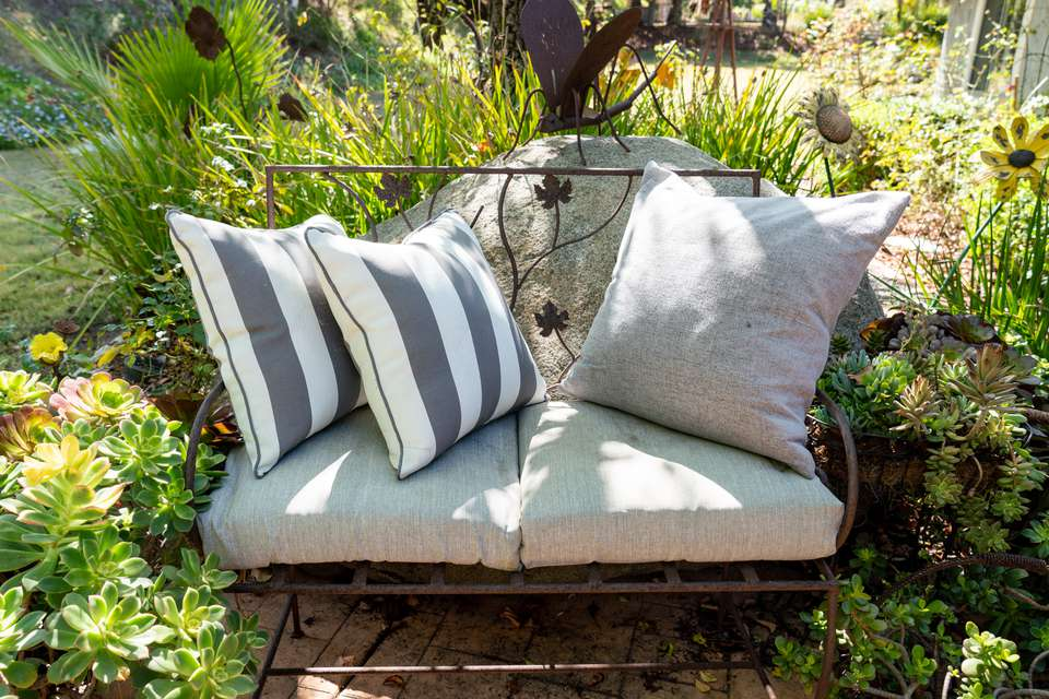 Outdoor seating with metal frame and light colored cushions in middle of garden