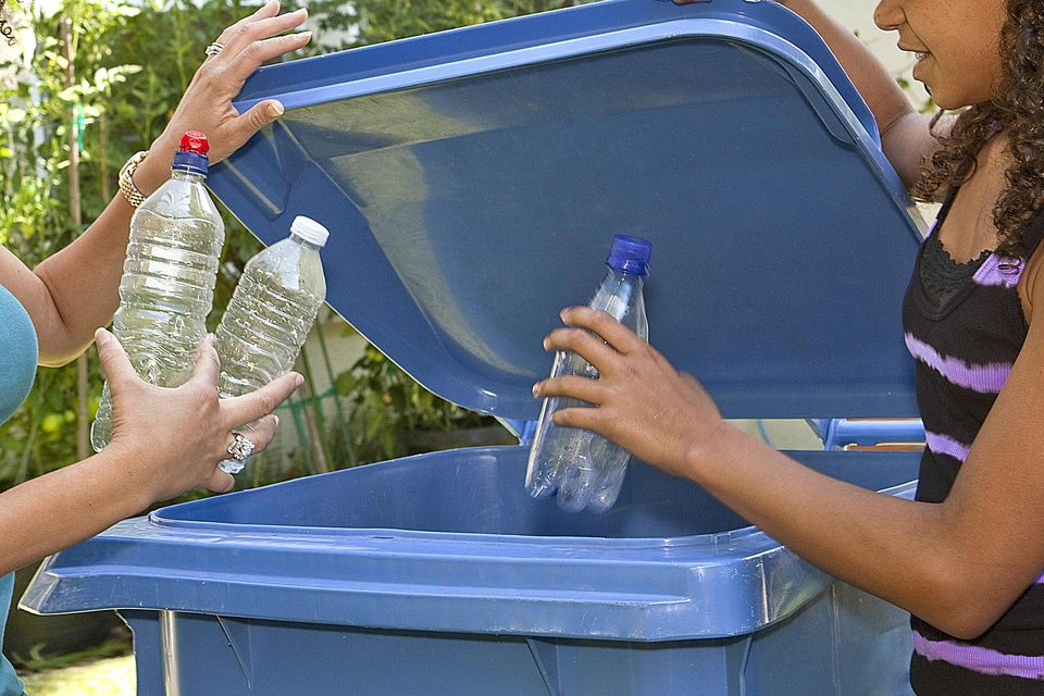Two women recycling plastic bottles
