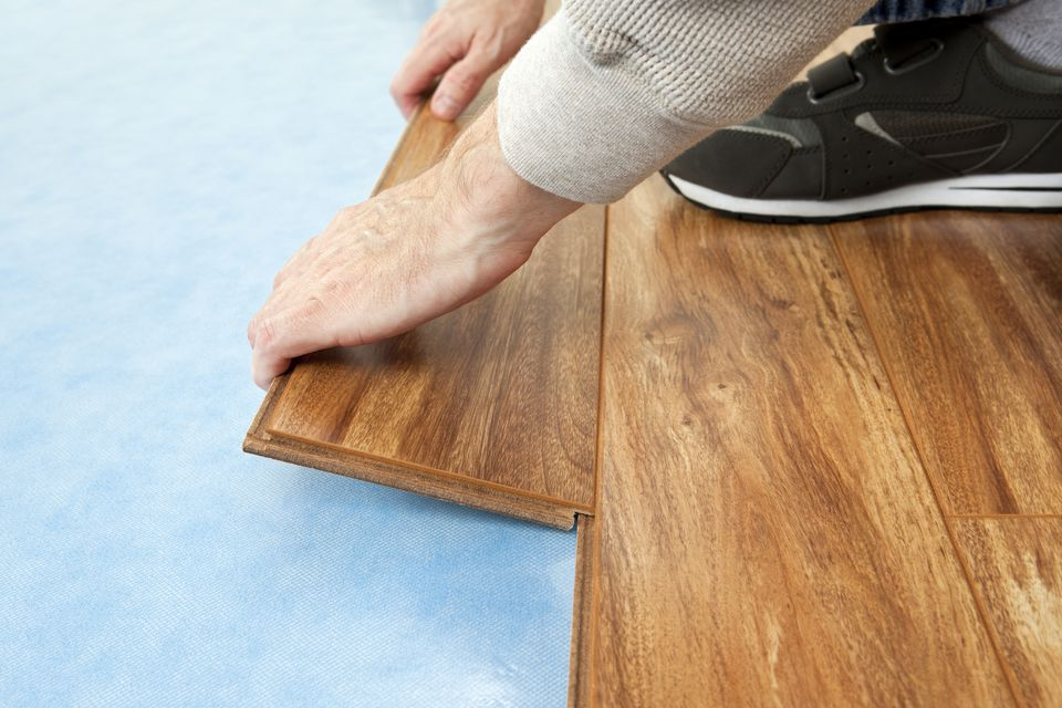 Hands Installing New Flooring Blue Foam Underlayment Provides