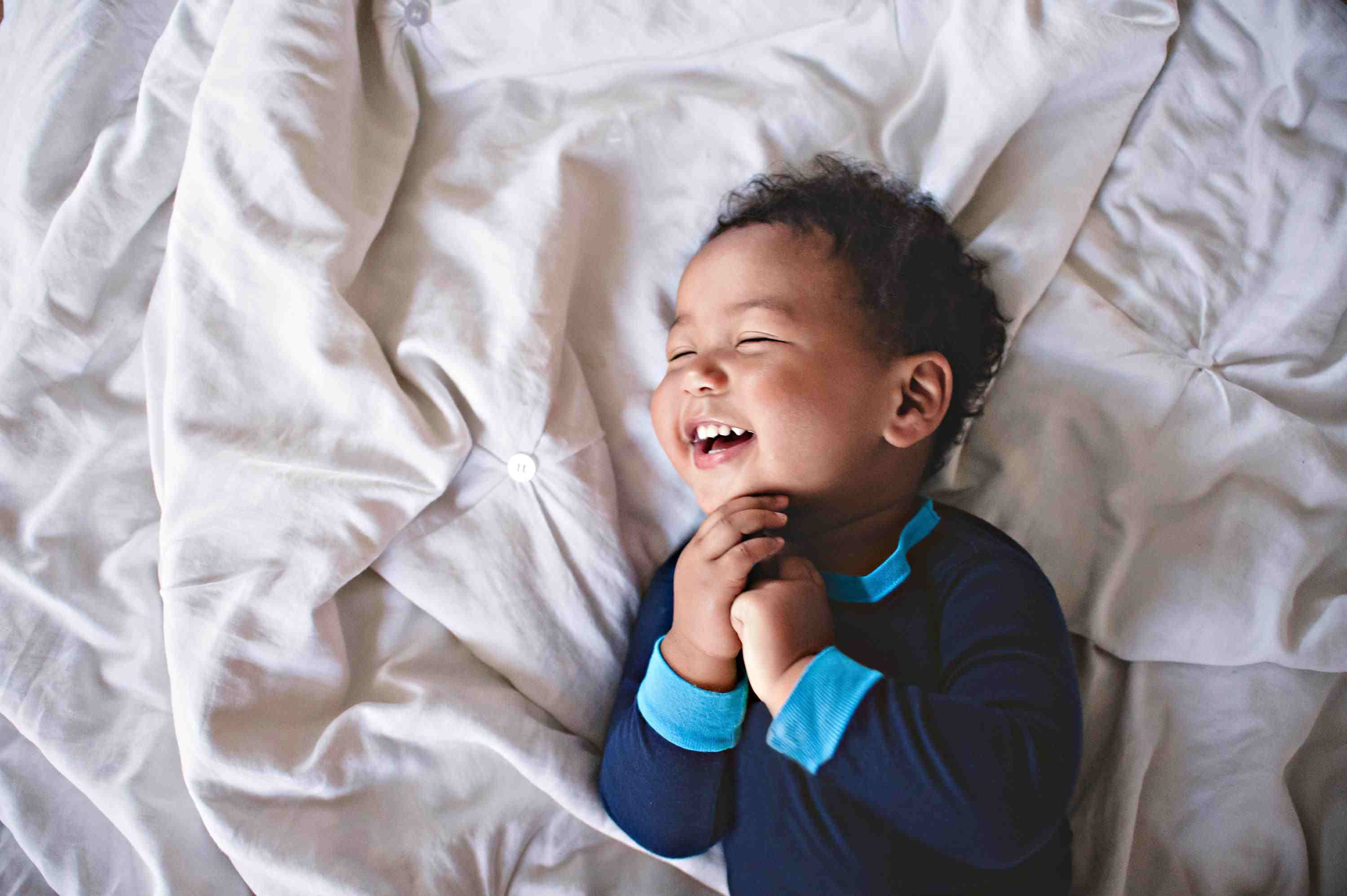 Happy Boy Laughing on Bed