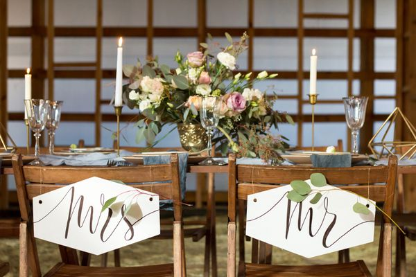 Wedding party. Laid Table by wedding banquet in a wooden barn. Candles and bouquet.