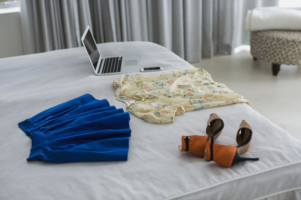 Clothing on bed being photographed for sale