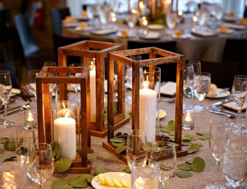 Linternas de madera en una mesa de recepción de bodas