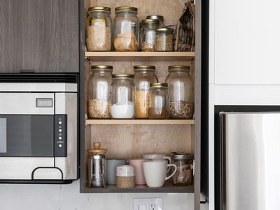 Kitchen pantry door opened with jars of spices and herbs and coffee mugs