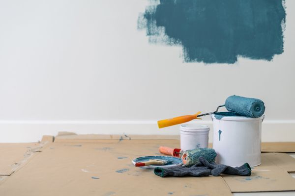 Painting supplies covered in blue paint next to partially painted white wall